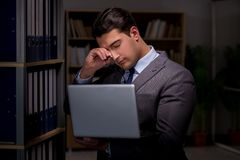 Businessman almost falling asleep working late hours in the offi. Ce Stock Photography