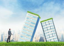 Businessman and falling buildings Royalty Free Stock Image