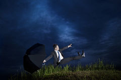 Businessman falling down in a cloudy day Royalty Free Stock Photography