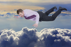 Businessman falling down over clouds in background Stock Photo