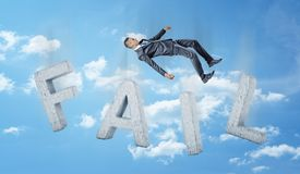 A businessman falling down in the sky on concrete letters forming a word FAIL. Business and work. Loss and failure. Corporate world Stock Photos