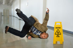 Businessman Falling on Wet Floor. African American businessman falling on wet floor in office Royalty Free Stock Photography