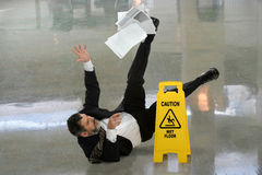 Businessman Falling on Wet Floor. Senior businessman falling on wet floor in front of caution sign Stock Images