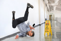Businessman Falling on Wet Floor Royalty Free Stock Image