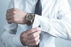 Businessman fastening buttons on shirt sleeve. Royalty Free Stock Images