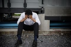 Businessman feel sad after geting fired. Young Asian male businessman, 20-30 years old, feel bad and fail after getting fired from work. he sit and hold his head royalty free stock photos