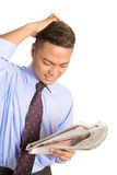 Businessman feeling despair with news. Young Asian businessman feeling despair as he reads about falling stock shares on money section of newspaper Stock Photos