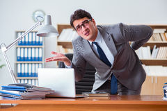 The businessman feeling pain in the office. Businessman feeling pain in the office Royalty Free Stock Images