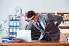 The businessman feeling pain in the office. Businessman feeling pain in the office Stock Photos