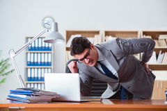 The businessman feeling pain in the office. Businessman feeling pain in the office Stock Images