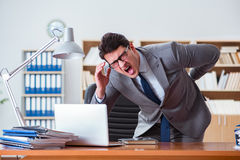 The businessman feeling pain in the office. Businessman feeling pain in the office Royalty Free Stock Photo