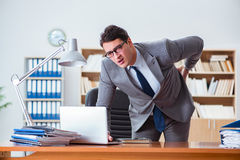 The businessman feeling pain in the office. Businessman feeling pain in the office Stock Photo