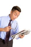Businessman feeling shock with news. Young Asian businessman express shock as he reads the money section of newspaper Royalty Free Stock Images