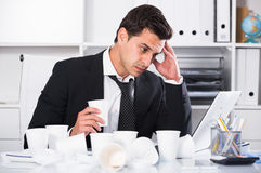 Businessman feeling thirsty in hot office. Businessman feeling thirsty and uncomfortable because of heat in office Stock Image