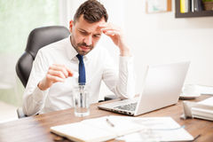 Businessman feeling unwell at work. Young businessman feeling unwell and dealing with a hangover with an effervescent tablet at the office Royalty Free Stock Photo