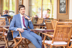 Businessman feels a discomfort sitting at cafe outdoor Stock Images