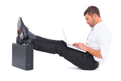 Businessman with feet up on briefcase Stock Photography