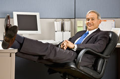 Businessman with feet up at desk Stock Photo