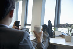 Businessman with feet up drinking coffee and text messaging Royalty Free Stock Photography