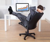 Businessman with feetup relaxing at computer desk Stock Photography