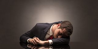 Businessman fell asleep at his workplace. Young businessman fell asleep at his workplace with copy space Royalty Free Stock Photo