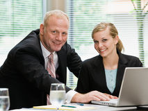 Businessman and female co-workers with laptop Royalty Free Stock Photo