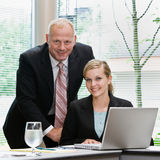 Businessman and female co-workers with laptop Stock Image