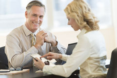 Businessman With Female Colleague Using Digital Tablet In Office Stock Photos