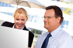 Businessman and Female Colleague Using Loptop Stock Image