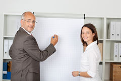 Businessman With Female Coworker Standing Near Flipchart Stock Image