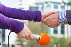 Businessman and a female reporter shaking hands before media interview Royalty Free Stock Photo