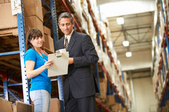 Businessman And Female Worker In Distribution Warehouse. Looking at clipboard stock images
