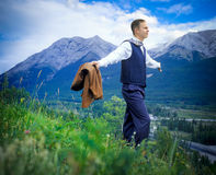 Businessman in field. With his arms raised Stock Photos