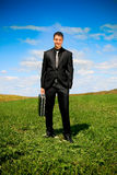 Businessman in the field. Young businessman outdoor holding a suitcase Stock Photo
