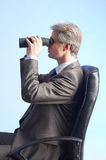 Businessman and field-glasses Stock Images