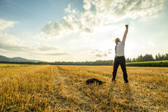 Businessman in the Field Raising Arm for Success Royalty Free Stock Image