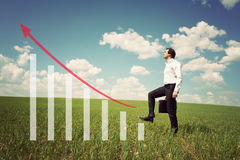 Businessman in the field rises on the chart with red arrow up Royalty Free Stock Photos