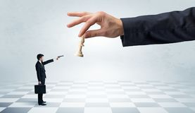 Businessman fighting against big chessman on a big hand. Small businessman fighting against big chessman on a big hand with chess board conceptn Stock Image