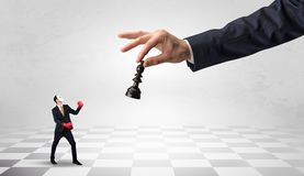 Businessman fighting against big chessman on a big hand. Small businessman fighting against big chessman on a big hand with chess board conceptn Royalty Free Stock Images