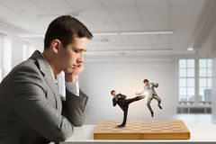 Businessman fighting on the chessboard Stock Images