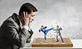 Businessman fighting on the chessboard. Businessman sitting at table and chessboard with fighting people Stock Images