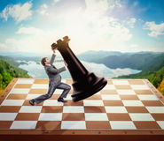 Businessman fighting with a chessman Royalty Free Stock Image