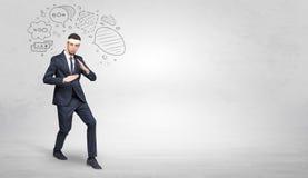 Businessman fighting with doodled symbols concept. Young businessman in suit fighting with doodled symbols concept stock image