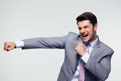 Businessman fighting over gray background Royalty Free Stock Images