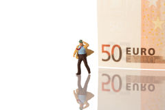 Businessman figurine running with euro banknote. Isolated on white with clipping path royalty free stock photography