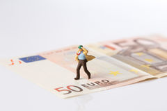 Businessman figurine running on a euro banknote. On white background stock image