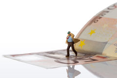 Businessman figurine running on a euro banknote. On white background with clipping path Royalty Free Stock Images