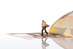 Businessman figurine running on a euro banknote. On white background with clipping path Royalty Free Stock Photo