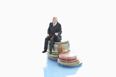Businessman  figurine sitting on stack of euro coins Royalty Free Stock Image