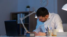 Businessman with files and laptop working at night stock footage